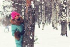 Menina no banco da rua do inverno fotografia de stock royalty free