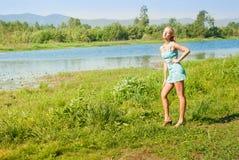 A menina no banco do rio Foto de Stock Royalty Free