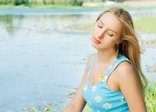 A menina no banco do rio Imagem de Stock Royalty Free