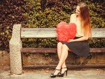 Menina no banco que guarda o coração Fotografia de Stock Royalty Free