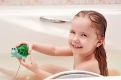 A menina no banho com um brinquedo Imagens de Stock Royalty Free