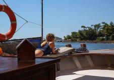 A menina no banho de sol do barco Imagens de Stock