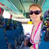 Menina no barramento de turista feliz com óculos de sol Imagem de Stock