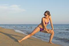 Menina no biquini que estica e que exercita na praia Fotos de Stock Royalty Free