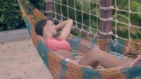 A menina no biquini vermelho brilhante com pés longos descansa na rede video estoque