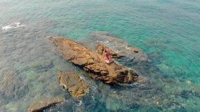 A menina no biquini vermelho senta-se na pedra enorme na mão de ondulação do mar vídeos de arquivo