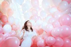 A menina no branco voa entre balões cor-de-rosa fotografia de stock royalty free