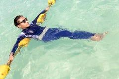 A menina no burkini azul relaxa em um mar de turquesa Imagem de Stock Royalty Free