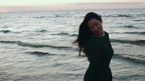 Menina no cabelo escuro da agitação do vestido na água na costa Photoshoot posing modelo Sea filme