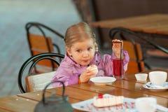 A menina no café que come o bolo Foto de Stock Royalty Free
