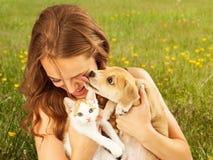 Menina no campo com gatinho e o cachorrinho afetuoso fotos de stock