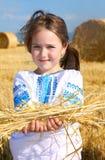 Menina no campo da colheita com pacotes da palha Fotografia de Stock