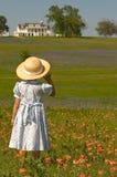 Menina no campo das flores com casa Foto de Stock