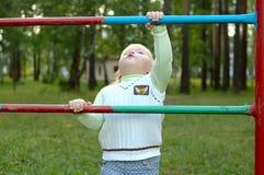 Menina no campo de jogos da criança no parque. Imagens de Stock Royalty Free