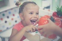 Menina no campo de jogos Menina feliz que joga com dinheiro das crianças Imagens de Stock