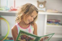 Menina no campo de jogos Livro ilustrado da leitura da menina Fotografia de Stock