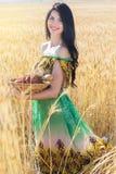 Menina no campo do centeio com a cesta dos bolos e dos rolos Imagens de Stock Royalty Free