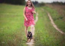 Menina no campo do verão corrido com cão Imagem de Stock