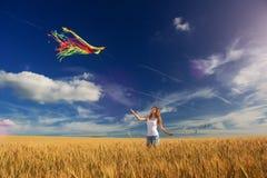 A menina no campo lança um papagaio Imagem de Stock