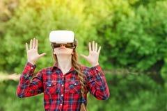 Menina no capacete da realidade virtual na perspectiva de foto de stock