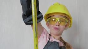 A menina no capacete e em óculos de proteção protetores, pensa sobre o projeto Infância, construção, arquitetura, construção video estoque