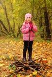 Menina no carrinho do parque do outono perto do portal oxidado Fotografia de Stock Royalty Free