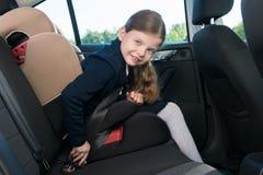A menina no carro antes de ir educar prende o cinto de segurança de seu assento imagens de stock royalty free