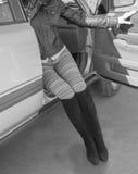A menina no carro com pés na rua , Preto e branco Foto de Stock Royalty Free