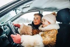Menina no carro como um motorista e um menino pequeno perto dela como um passanger foto de stock