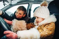 Menina no carro como um motorista e um menino pequeno perto dela como um passanger imagens de stock royalty free