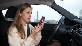 A menina no carro lê a mensagem no telefone e nas quedas frustrados no volante 4K Mo lento video estoque