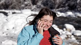 A menina no casaco azul em um dia de inverno ensolarado anda o lago na floresta e fala pelo telefone filme