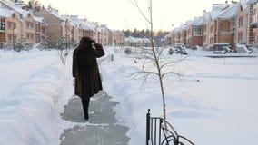 Menina no casaco de pele do passeio traseiro na vila do inverno vídeos de arquivo