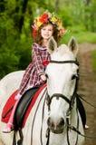 Menina no cavalo de equitação floral da grinalda imagens de stock royalty free