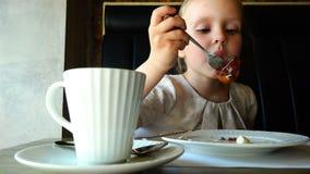 A menina no chá bebendo da tabela e come o bolo de uma placa filme