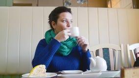 Menina no chá bebendo do café, senta-se na tabela e olha-se para fora a janela video estoque