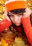 Menina no chapéu alaranjado nas folhas. Depressão do outono. imagem de stock