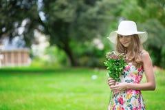 Menina no chapéu branco que guarda o grupo de flores Imagens de Stock