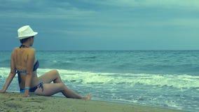 A menina no chapéu branco senta-se no litoral durante uma tempestade pequena filme