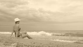 A menina no chapéu branco senta-se no litoral durante uma tempestade pequena vídeos de arquivo