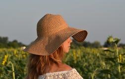 A menina no chapéu de palha no perfil no campo com girassóis imagens de stock royalty free