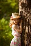 Menina no chapéu de palha que está perto de uma árvore Fotos de Stock Royalty Free