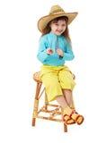 Menina no chapéu de palha que senta-se na cadeira de madeira Imagem de Stock Royalty Free