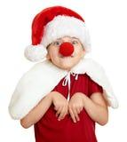Menina no chapéu de Santa com o nariz do palhaço no branco isolado Imagens de Stock Royalty Free