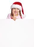 Menina no chapéu de Santa com placa branca Foto de Stock