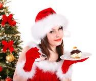 A menina no chapéu de Santa come o bolo pela árvore de Natal. Imagem de Stock