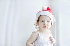 Menina no chapéu de Santa, em um fundo claro perto da janela fotografia de stock
