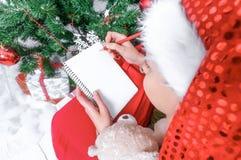 A menina no chapéu de Santa escreve a letra a Santa perto da árvore de Natal imagens de stock