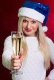 Menina no chapéu de Santa na camiseta branca que sorri com um vidro do campeão Fotografia de Stock Royalty Free