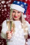 Menina no chapéu de Santa na camiseta branca que sorri com um vidro do campeão Imagem de Stock Royalty Free